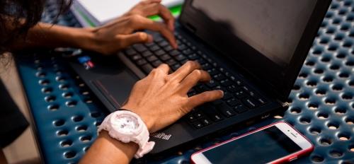 A high schooler's hands working on a laptop