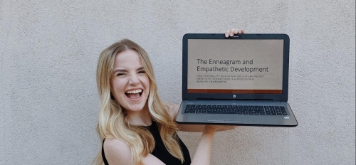 Claire holding up a laptop on a screen related to her field of study