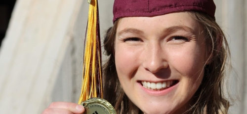 Lindsay Lohr in her ASU cap and gown holding her Dean's medal