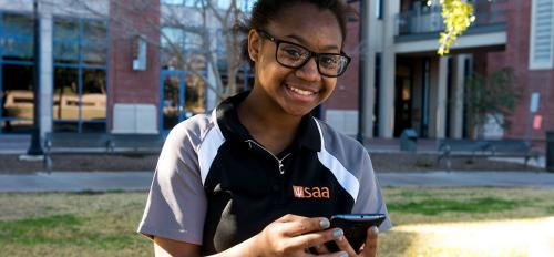 Female student holding Android device with ASU Learn to thrive app