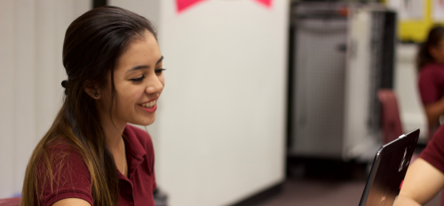 A middle school female student grins at her computer at ASU Prep Phoenix Middle School.