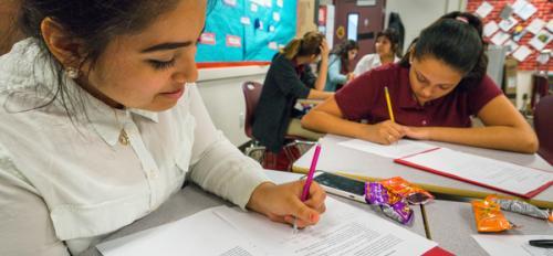high school girls writing in classroom