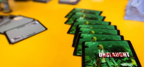The pieces of a student-created zombie board game are displayed on a table.