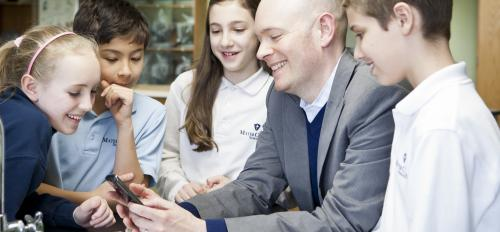 A man shows children what's on his smart phone.