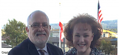 middle-aged man and woman smiling at the camera with American flags in the background