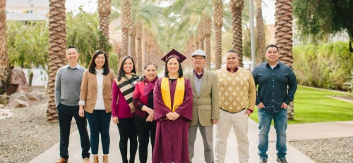 A woman in a cap and gown poses on Palm Walk with her family