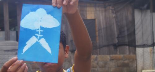 A Honduran child holds up a blue and white cyanotype of a plant