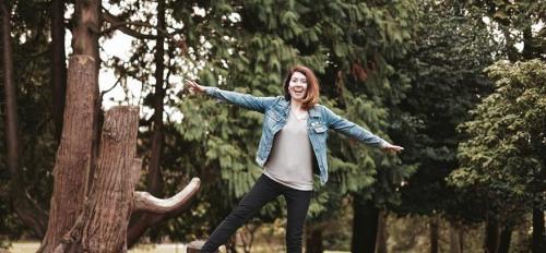 Courtney Baxter stands on a log