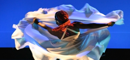 Woman dancing in a white dress as it twirls around her body.