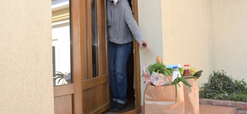A person wearing a mark reaches for grocery bags outside residence door