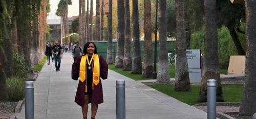 ASU student in cap and gown on Palm Walk