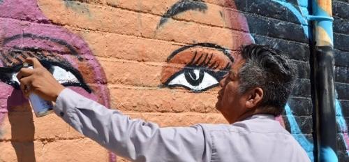 Douglas Miles paining a mural of an Apache woman.