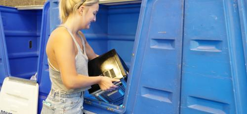 Photo of ASU student recycling item during Ditch the Dumpster