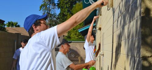 Volunteers lay a new coat of paint over the outside walls.