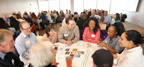 Community members talk around a table
