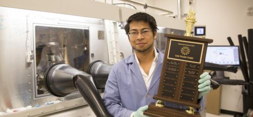 Photo of Sebastian Husein holding a trophy in a lab.