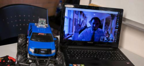 A student poses on a laptop webcam feed next to a remote controlled car during a project demonstration.