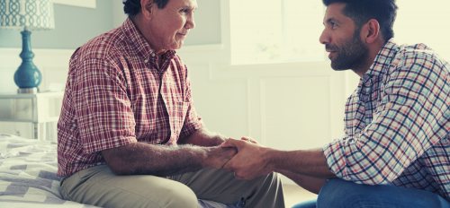 A son who serves as a family caregiver for his elder father, holds his hands as they look at each other. Both men are wearing plaid shirts with bold colors.