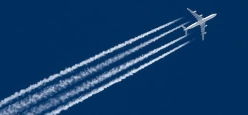 A plane flying with contrails.