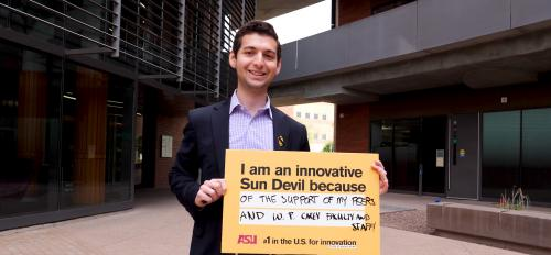 "man holding sign that says ""I am an innovative Sun Devil because of the support of my peers and W. P. Carey faculty and staff!"""
