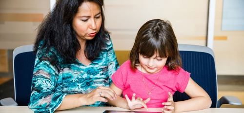 woman shows young girl EMBRACE app on tablet