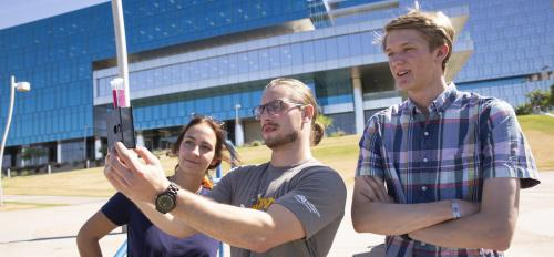 Three students test water quality