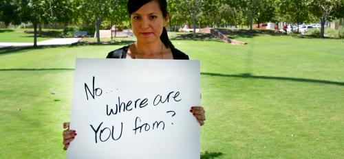 "woman holding a sign displaying a ""microaggression"""