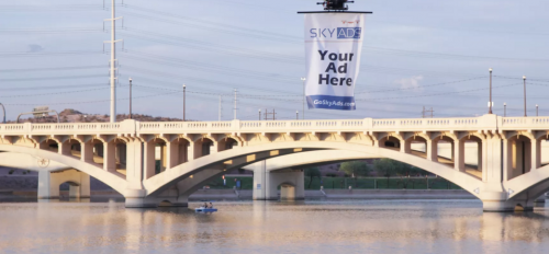 A drone carries a banner ad over Tempe Town Lake