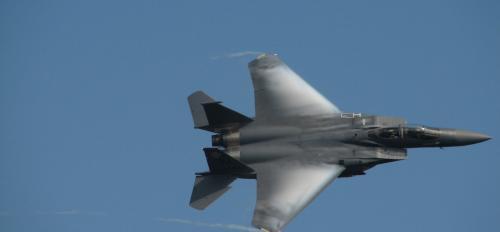 F-15 jet flies through the blue sky.