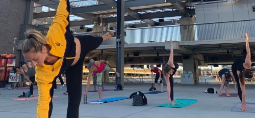 Yoga instructor leads stadium yoga on the sun deck with guests in background