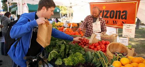 student picking out produce at food stand