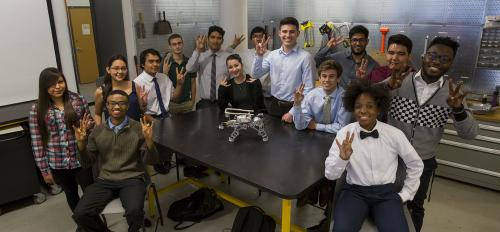 """A group of ethnically diverse students gather around a table, displaying the """"pitchfork,"""" Arizona State University's signature hand gesture. On the table sits a LEGO robot, and the students are surrounded by tools and equipment."""