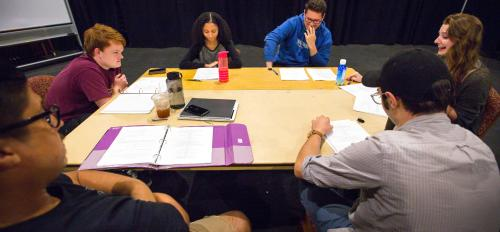 Student actors do a read-through around a table.