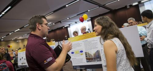 "Photo of female student talking with a man in front of a poster with a caption of ""Sharing your research and ideas at the FURI Symposium are part of the experience for undergraduate researchers like Emily Ford (right). Photographer: Jessica Hochreiter/ASU"