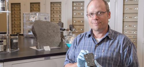 Professor Laurence Garvie holds meteorite.