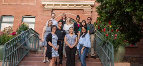 A group of students poses on the steps to the University Club building.