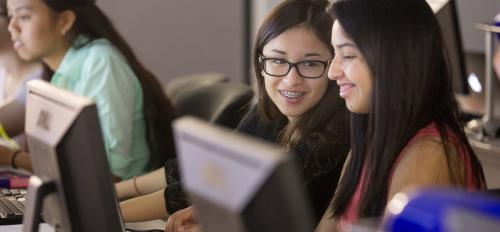 Smiling high school girls study STEM in a computer lab.