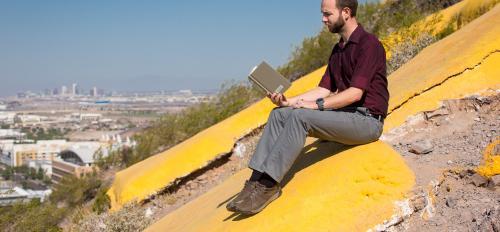 man reading book on mountain