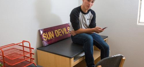 ASU student sitting on his dorm room desk