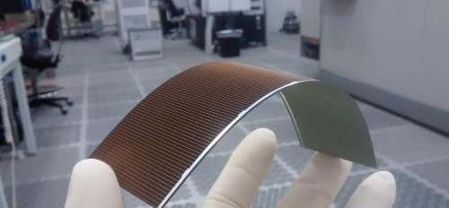A gloved hand holds a flexible solar cell in a lab.