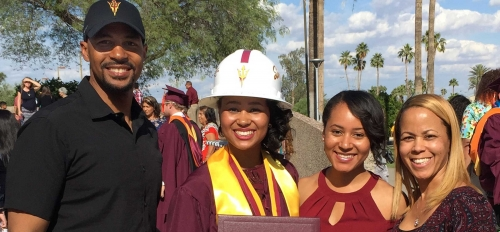 A woman in a graduation gown and construction hat stands with her family at a 2017 ASU graduation