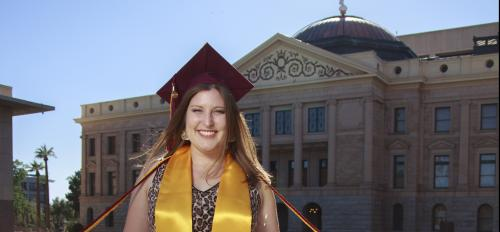 Aly Perkins (light complexion with medium brown hair, wears sleeveless dress, maroon mortar board, maroon and gold cords, and gold stole of gratitude) stands smiling in front of Arizona Capitol building
