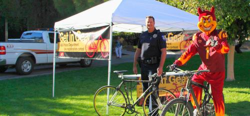 A police officer and Sparky on a bike stand outside near a pop-up tent.