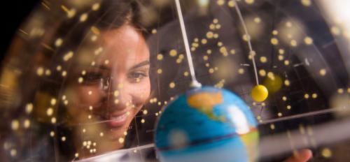 Woman looks through a clear globe