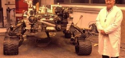 man standing in front of Mars rover replica