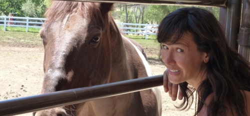 ASU School of Social Work Associate Professor Joanne Cacciatore smiles while posing with a horse
