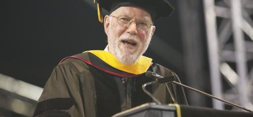 commencement speaker at podium addressing graduates