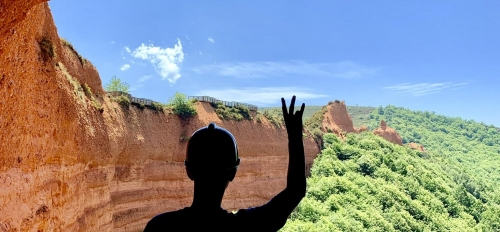 A silhouette of an ASU student holding up a pitchfork overseeing a landing with a forest below in Spain