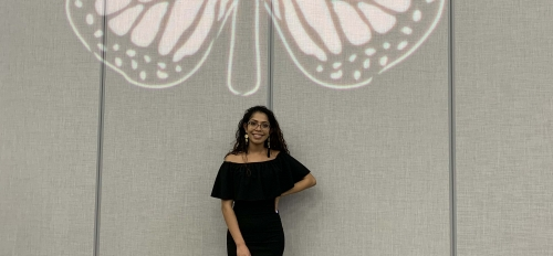 Karina Dominguez stands in front of a butterfly projection