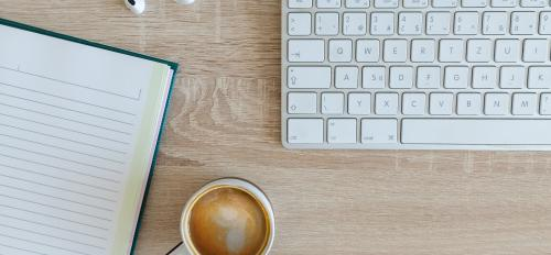 photo of keyboard with coffee mug and notebook